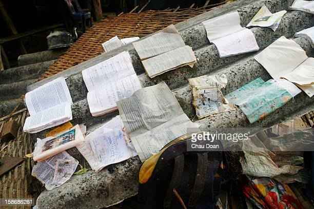 School books are laid out to dry on the roof of a collapsed house in Trung Don village Hai Thanh commune Hai Lang district Quang Tri province Vietnam...
