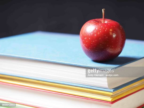 school books with apple - andy clement stock pictures, royalty-free photos & images