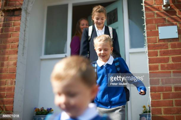school boy and sisters leaving front door - leaving stock pictures, royalty-free photos & images