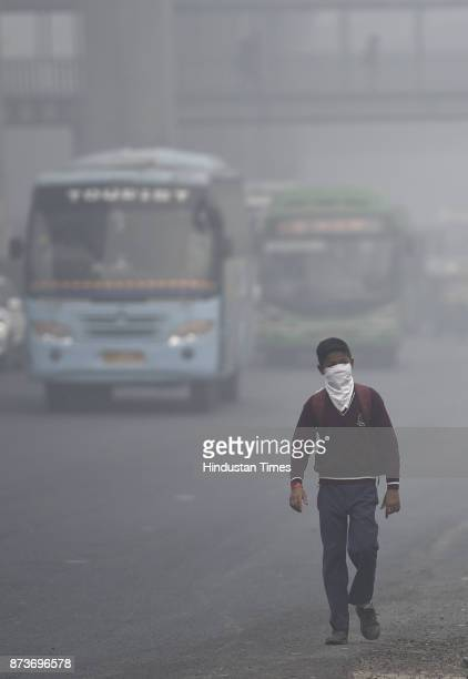 A school boy covers his nose and mouth as he walks along a busy road on a smoggy day at Moti Bagh on November 13 2017 in New Delhi India The air...