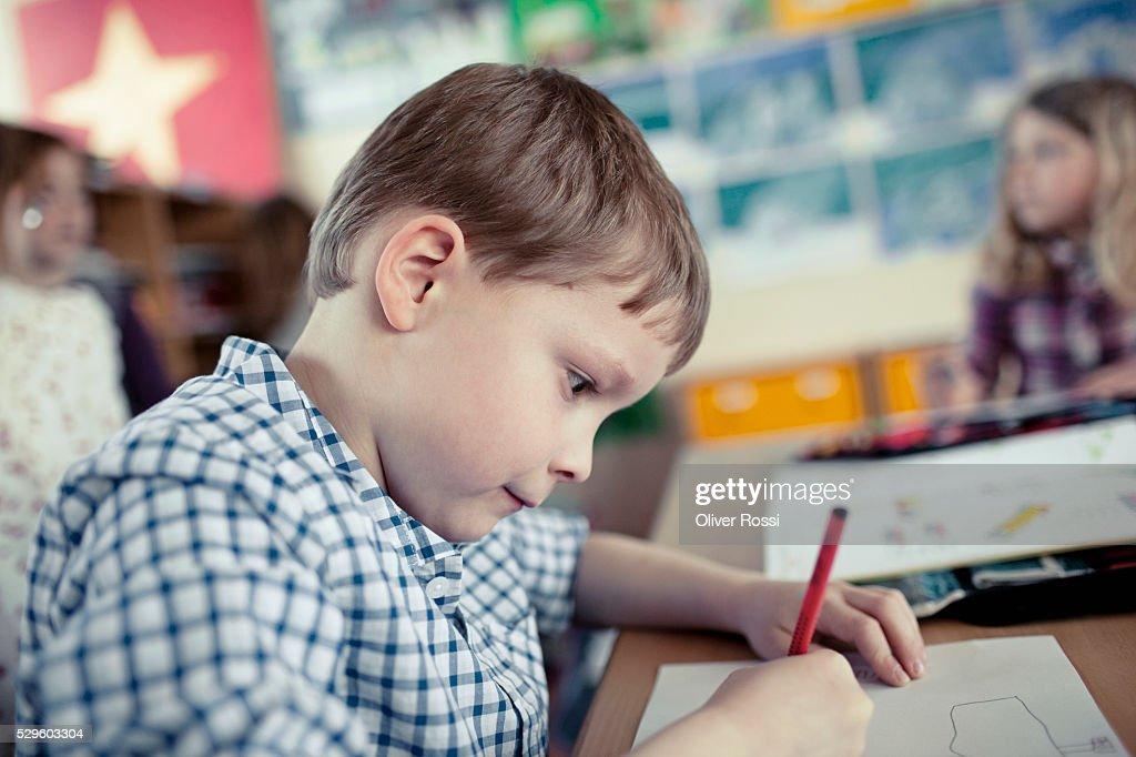 School boy (8-9) drawing during art class : Stock-Foto
