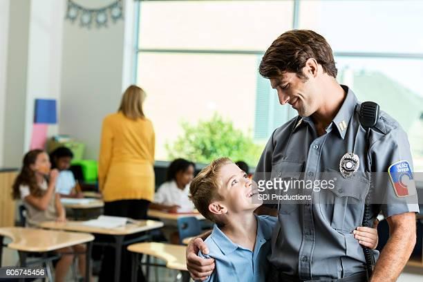 School boy gives policeman a hug
