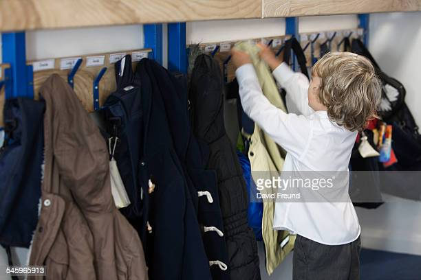 school boy hanging up his coat - coat stock pictures, royalty-free photos & images