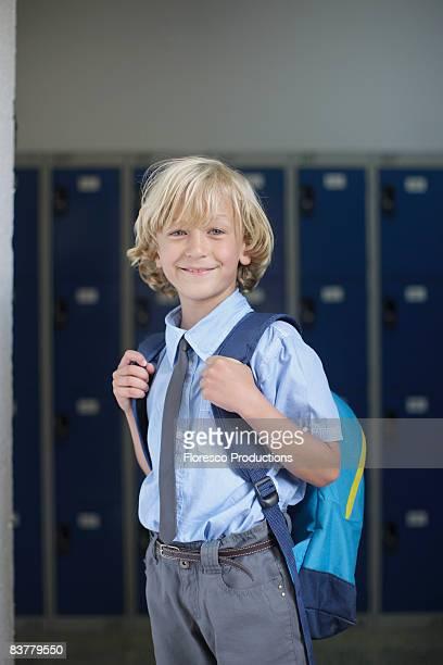 School boy holding backpack