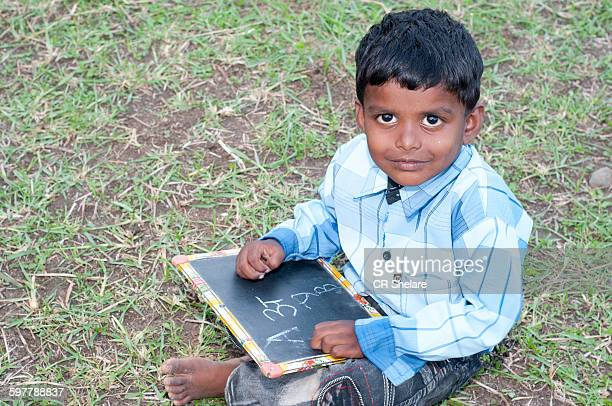 School boy holding slate with English alphabet