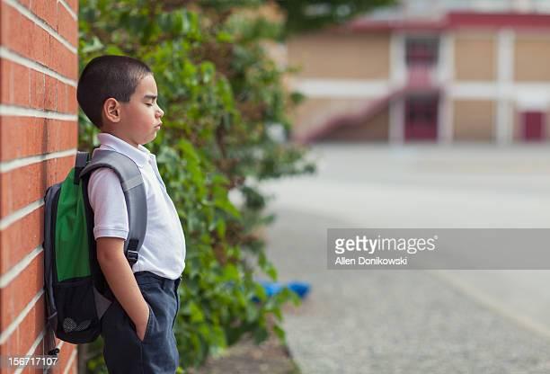 school boy leaning against red brick wall