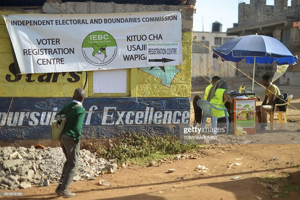 A school boy looks at a banner advertising a voter-registration point January 18, 2017 as he walks past as Interim Electoral and Boundaries Commission (IEBC) clerks capture the biometric details of a voter at Baba-Dogo slum area of Nairobi. Leaders across the political divide have intensified the push to have their supporters register as voters ahead of what is billed as a do or die election scheduled for August this year. Strategies to encourage their supporters to register, include calls for no registration no sex in Mombasa and 'no boda boda (motor-bike taxi)services' for unregistered residents at lakeside city Kisumu. / AFP / TONY