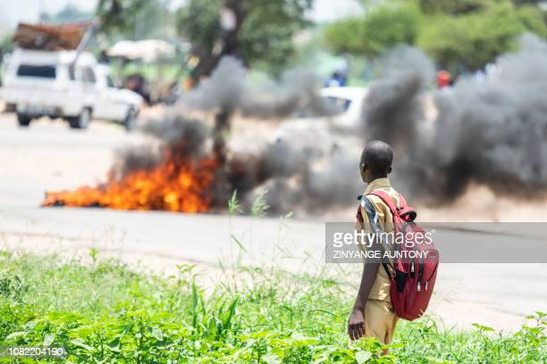 TOPSHOT A school boy looks at a burning barricade during a shutdown demonstration on January 14 2019 in Bulawayo after the president announced a more...