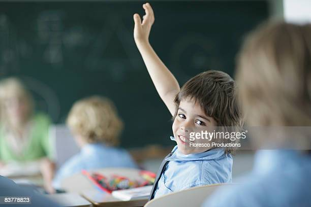 school boy raising hand in class - hands up stock photos and pictures