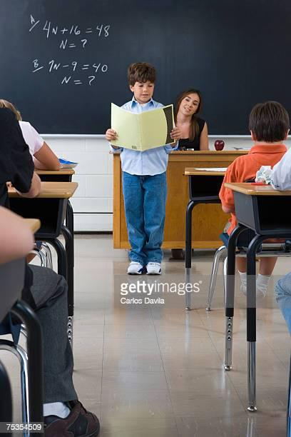 School boy (6-7) reading in front of class of school children (10-13)