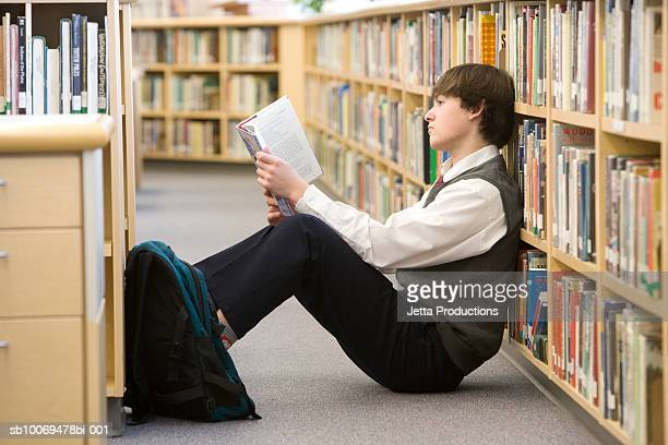 School boy (16-17) reading on floor by bookshelf in library