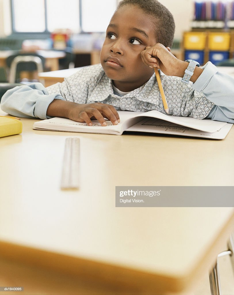 School Boy Sits at a Table With an Exercise Book, Listening and Looking Sideways : Stock Photo