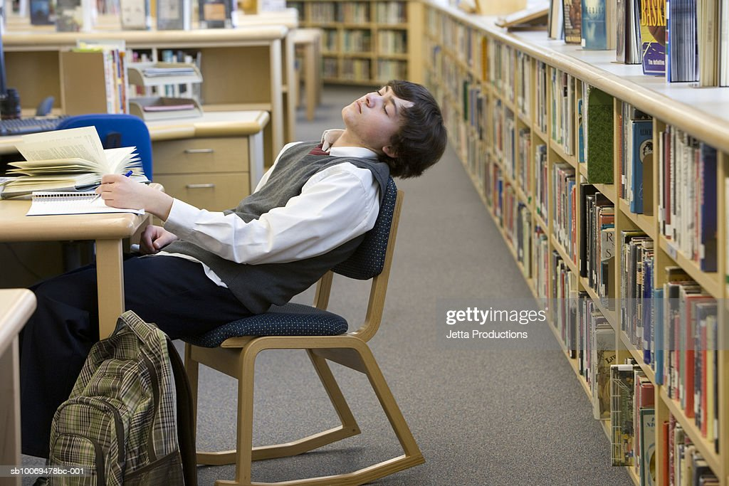 School boy (16-17) sleeping at desk in library : Stock Photo