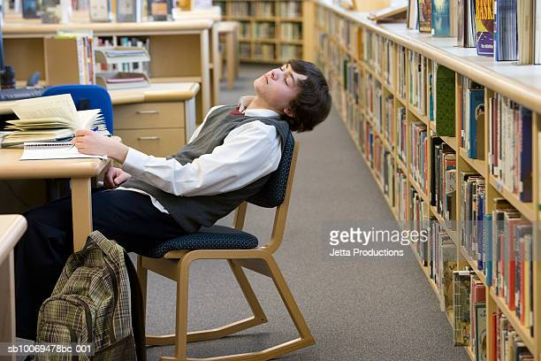 School boy (16-17) sleeping at desk in library
