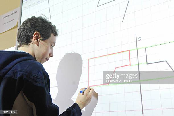 A school boy uses a digital 'whiteboard' during a geometry class on symetry at the Vande Borne primary school in Jette Brussels on March 12 2008 The...