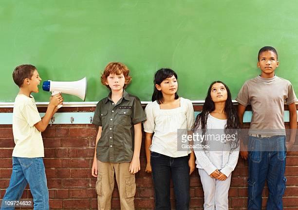 Schule Junge mit einem Megafon ruft. in Klassenkameraden