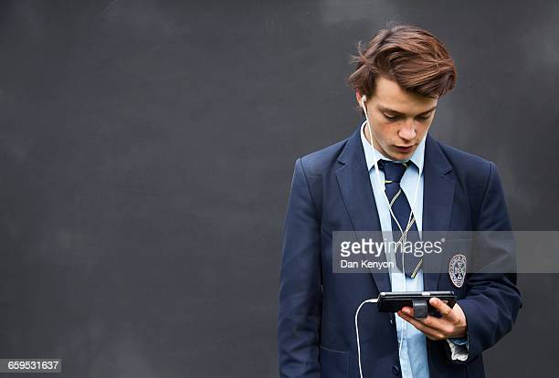 School boy with headphones and handheld device