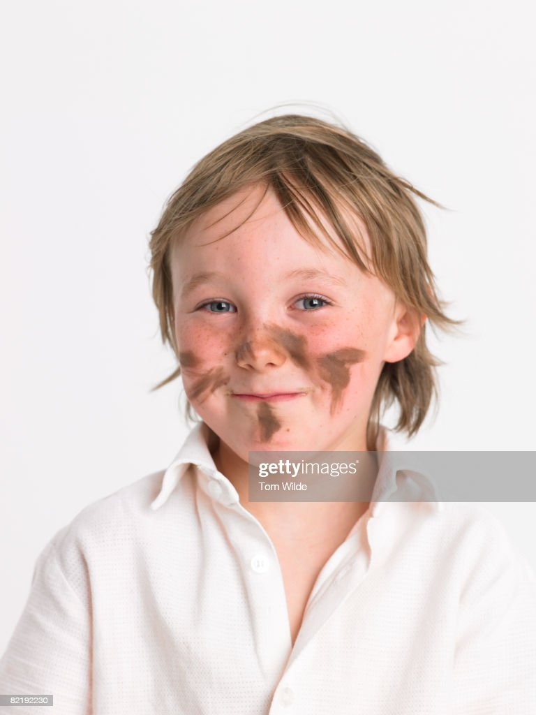 School boy with mud on face : Stock Photo