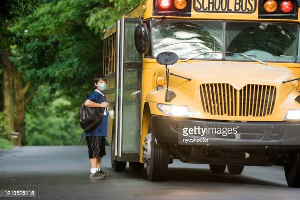 school boy with surgical mask at bus stop. - school bus stock pictures, royalty-free photos & images