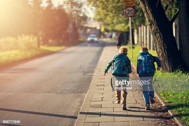 school boys running to school - schoolboy stock pictures, royalty-free photos & images