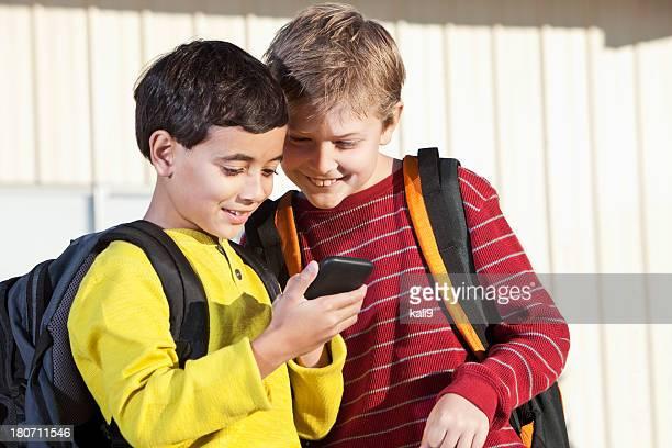 男子学生のモバイル機器を使用する
