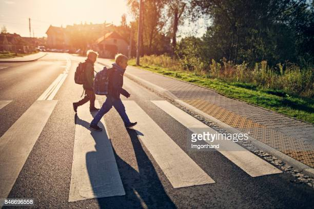 school boys walking on zebra crossing on way to school - pedestrian crossing stock photos and pictures
