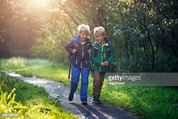 school boys walking to school - satchel bag stock photos and pictures