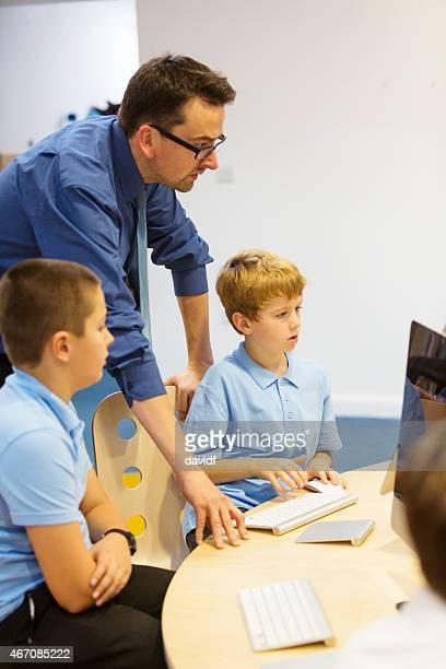 Garçon avec professeur à l'école et ordinateur