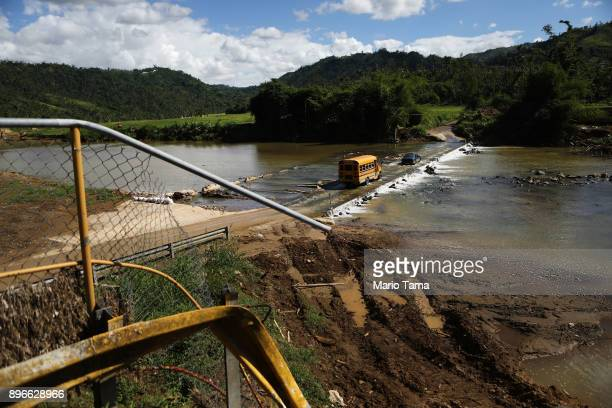 A school bus crosses a makeshift bridge for vehicles near where the original bridge was washed away by Hurricane Maria flooding on December 20 2017...