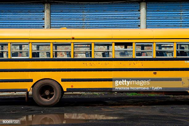 School Bus On Street Against Wall