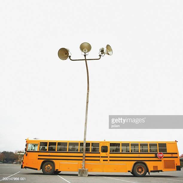 school bus parked by light pole (digital enhancement) - モデスト ストックフォトと画像