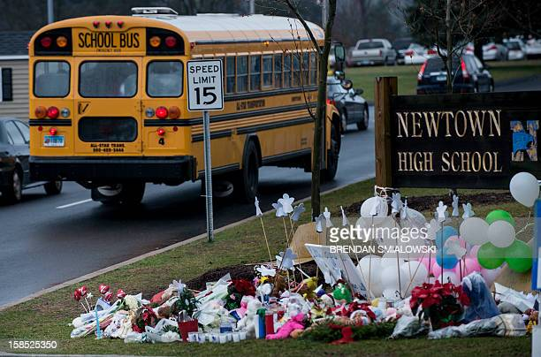 A school bus passes a makeshift memorial to the victims of the Sandy Hook Elementary School shooting as it takes students to Newtown High School...
