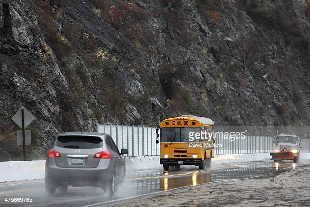 A school bus passes below a charred hillside in the Colby Fire burn area as a storm brings rain in the midst of record drought on February 28 2014...