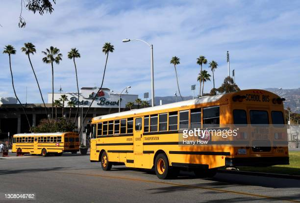 School buses bring in players from the Burbank Bulldogs and the Pasadena Bulldogs before their game at Rose Bowl on March 19, 2021 in Pasadena,...