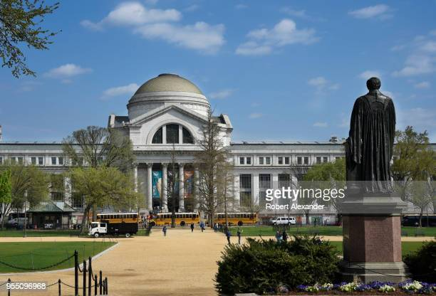 School buses unload visiting students in front of the National Museum of Natural History in Washington, D.C. Facing the museum is a statue of the...