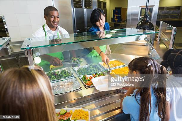 School cafeteria workers offering healthy food options to students