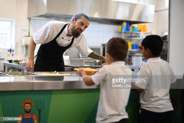 School chef serves cooked hot dinner to students on their lunch break at St Luke's Church of England Primary School in East London on September 3,...
