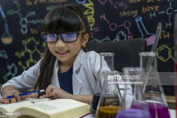 school chemical experiment. school education.girl cute school pupil play with test tubes and colorful liquids. - stereotypical stock pictures, royalty-free photos & images