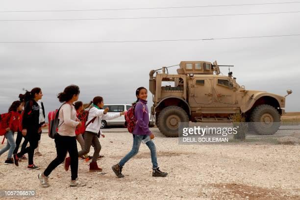 School chikldren walk past a US military vehicle in the Kurdishheld town of AlDarbasiyah in northeastern Syria bordering Turkey on November 4 2018...