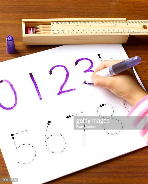 School child age 4-7 learning shapes of numbers.