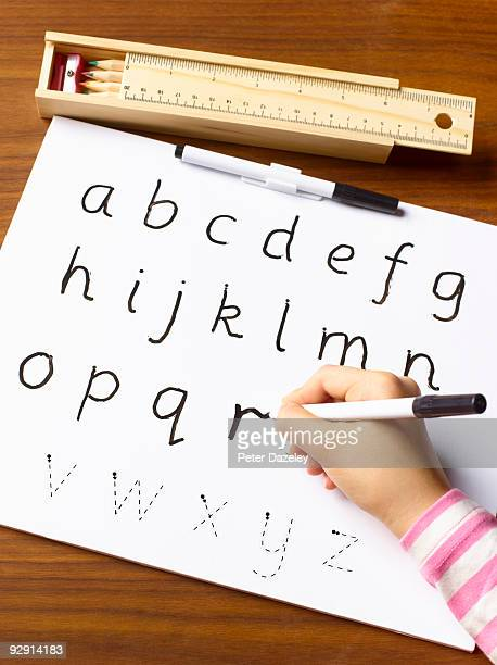 School child age 4-7 learning to shape letters.