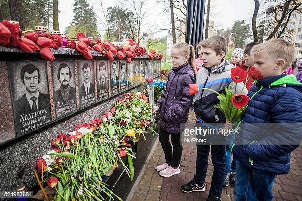 School child looks the carved stones in the memorial to Chernobyl firefighters in Slavutych Ukraine on April 26 2016 Slavutych is a city in the north...