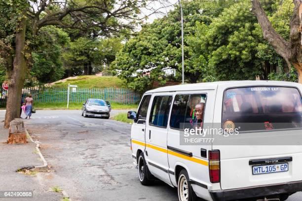 Niño de escuela que viajan con la cabeza por la ventana del taxi