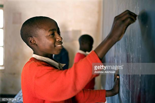 A school child writing on the blackboard during class at Ikuna village primary school near to Iringa in Tanzania They are having a class run by a...