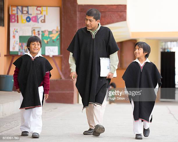 school children (6-7) and male teacher wearing traditional ecuadorian costume, ecuador - hugh sitton stock-fotos und bilder