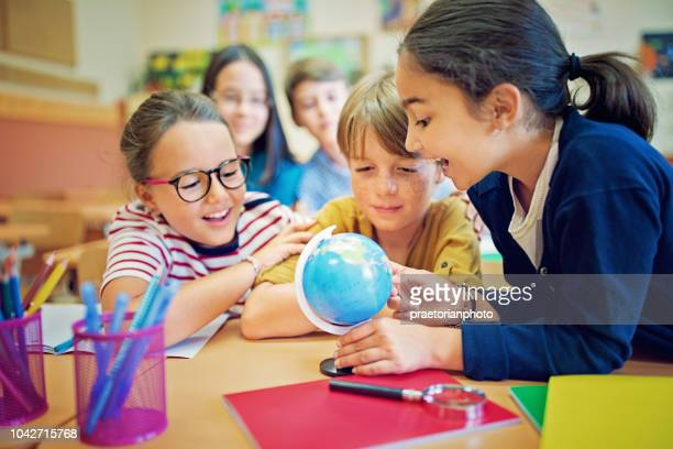 SchülerInnen und Schüler untersuchen eine Kugel im Klassenzimmer
