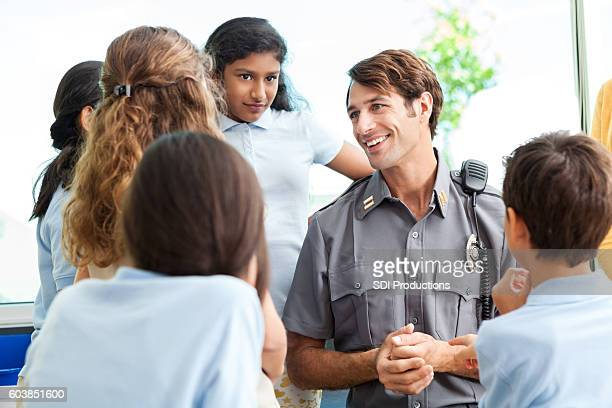 School children ask police officer questions