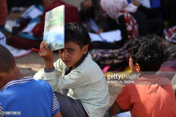 School children attend an open-air class under a tree near their unfinished school on September 16, 2019 in the southwestern Yemeni village of...