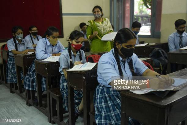 School children attent their class inside a school after authorities relaxed the lockdown norms and reopened educational institutions in Amritsar on...