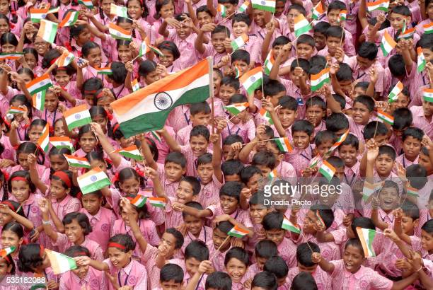 School children celebrate Indian Independence Day by waving Indian tri color flags in Mumbai, Maharashtra, India.